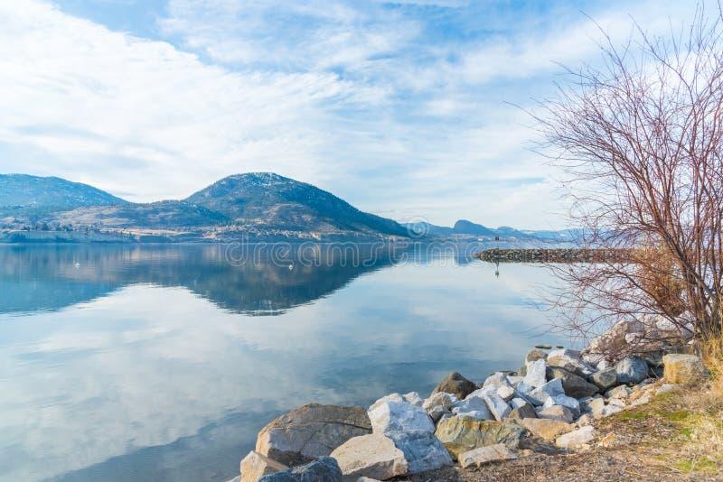 Felsige Küstenlinie des Wellenbrechers mit reflektierendem Himmel und Bergen des ruhigen Sees im Vorfrühling lizenzfreie stockfotos