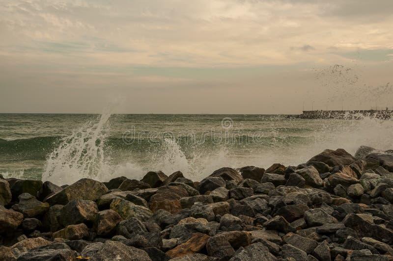 Felsige wilde Küste des Ozeans Wellen mit spritzt das Brechen auf dem Ufer verlassenes Dock im Hintergrund stockfoto