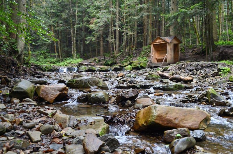 Felsiger Gebirgsfluss mit Gazebo im Wald lizenzfreies stockfoto