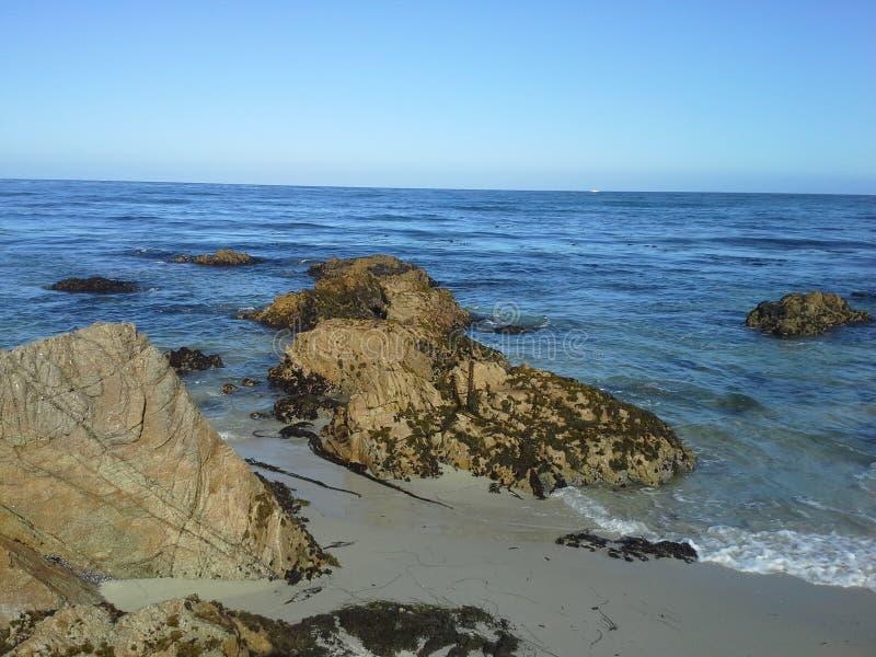 Felsiger Strand auf blauem Ozean mit klarem blauem Himmel lizenzfreie stockfotos