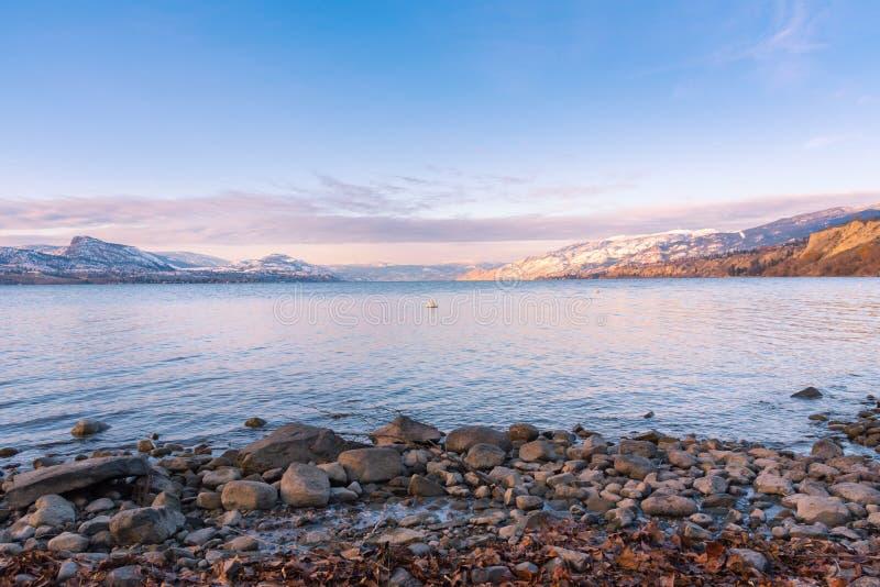 Felsiger Strand mit See und Schnee bedeckte Berge bei Sonnenuntergang lizenzfreie stockfotos