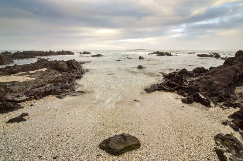 Felsiger Strand und Wolken stockfotografie