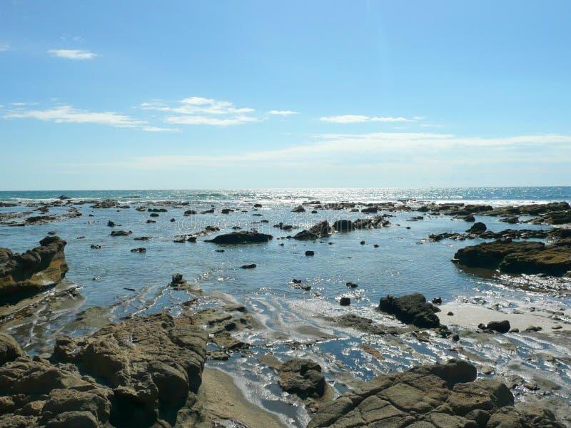 Felsiger u. sandiger Strand mit blauem bewölktem Himmel Israel lizenzfreies stockbild