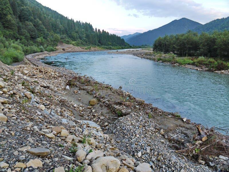 Felsiges Ufer von einem Gebirgsfluss, umgeben durch einen dichten grünen Wald und Bäume gegen einen bewölkten Himmel und entfernt stockfoto