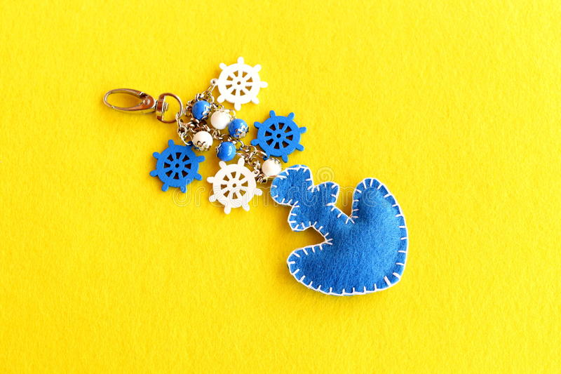 Felt anchor key chain decorated with beads and small decorative ship wheel. Charm accessory. Summer DIY idea royalty free stock photography