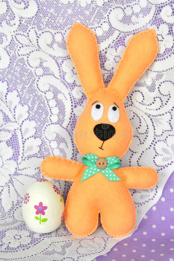 Felt beige rabbit and an decoupage egg - Easter symbols stock photography