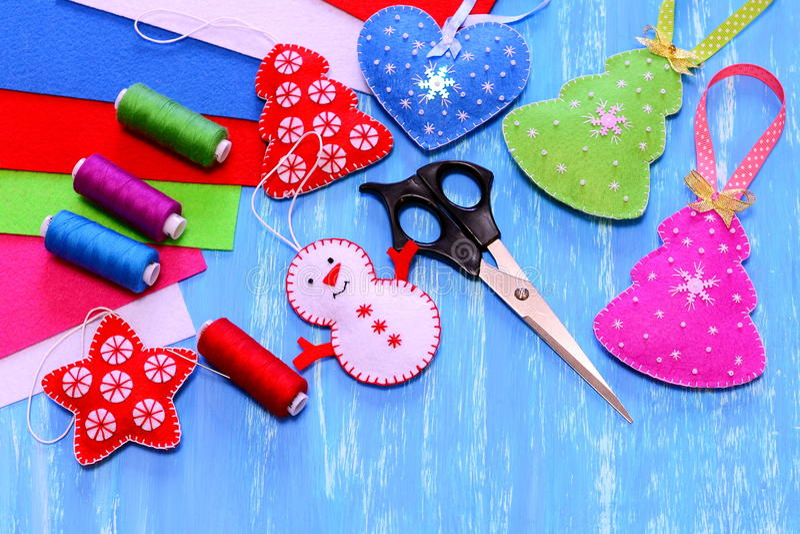 Felt Christmas ornaments. Christmas tree, heart, star, snowman crafts, scissors, sewing kit, felt sheets on blue wooden background stock image