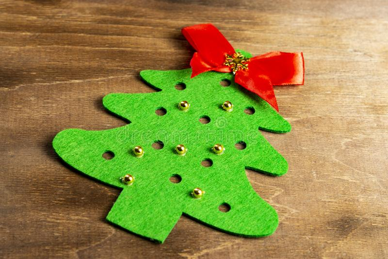 A felt christmas tree made by hands with golden bead toys and a red bow at the top lies on a wooden table. Christmas Craft.  stock photo