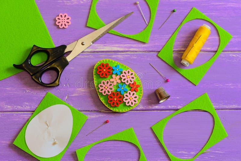 Felt Easter egg decor idea. Handmade felt Easter egg with colored wooden flower buttons. Felt scrap, scissors, thimble, thread. Felt Easter pattern. Tutorial stock image