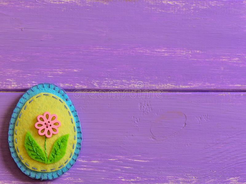 Felt Easter egg decor with pink flower on a wooden background with copy space. Fun Easter crafts for kids. Happy Easter. Easter crafts for kids. Fun DIY idea royalty free stock images