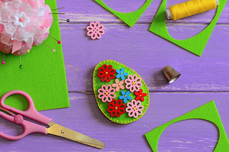 Felt Easter egg decor. Felt Easter egg decor with wooden flower buttons. Felt scrap, scissors, thimble, thread, pins. Easter crafts for elementary students royalty free stock photography