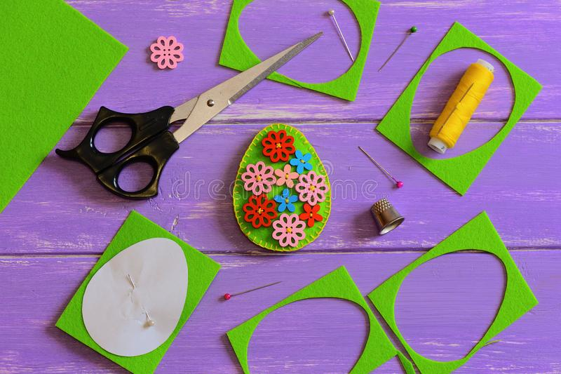 Felt Easter egg decoration. Handmade felt Easter egg with wooden flower buttons. Felt scrap, scissors, thimble, thread. Easter crafts for elementary students stock photo