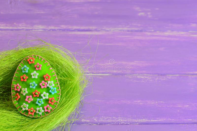 Felt Easter egg ornament with plastic flowers. Felt egg in the nest and on purple wooden boards with empty place for text. Quick Easter decoration ideas diy. How stock images