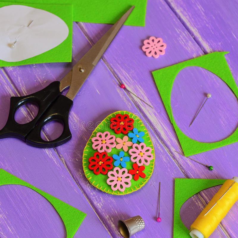 Felt Easter egg decoration idea. Hodemade felt Easter egg with colored wooden flower buttons. Felt scrap, scissors, thimble. Felt Easter pattern. Tutorial felt stock images