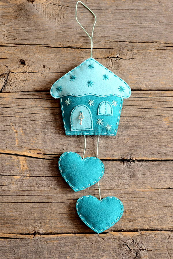 Felt house with hearts decor on old wooden background for Decorating ideas for wall cutouts