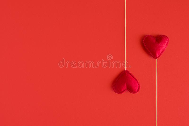 Felt love hearts on booth props on red paper background. Valentine`s day celebration concept. Top view. Flat lay. Copy space.  royalty free stock image