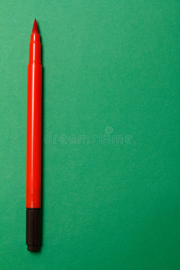 Felt marker. Red felt marker on green construction paper background stock image