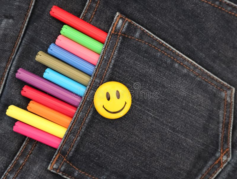 Felt pens in the pocket of gray jeans and smile. The concept of creative materials that are always at hand. The concept of joy from creativity royalty free stock photo