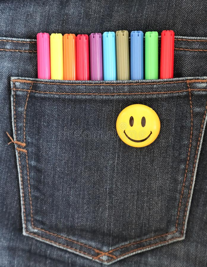 Felt pens in the pocket of gray jeans and smile. The concept of joy from creativity. Felt pens in the pocket of gray jeans and smile. The concept of creative stock photography