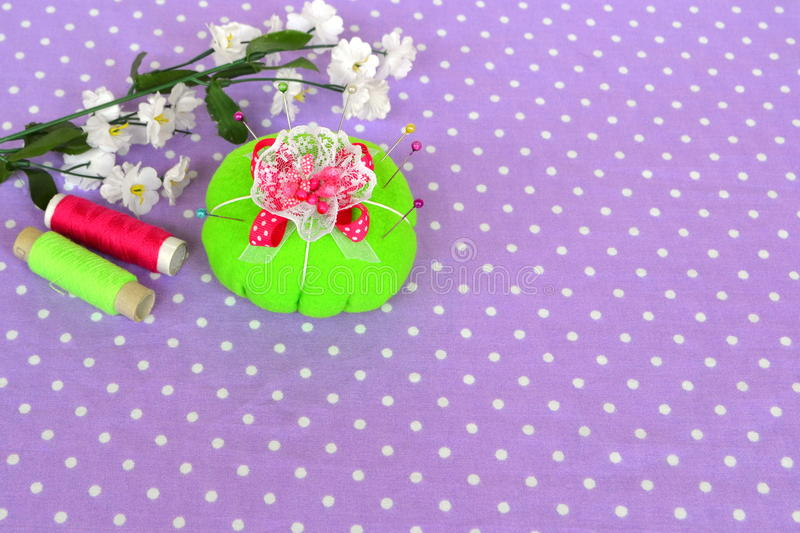 Felt pincushion with lot of pins for sewing. Background with empty place for text stock photos