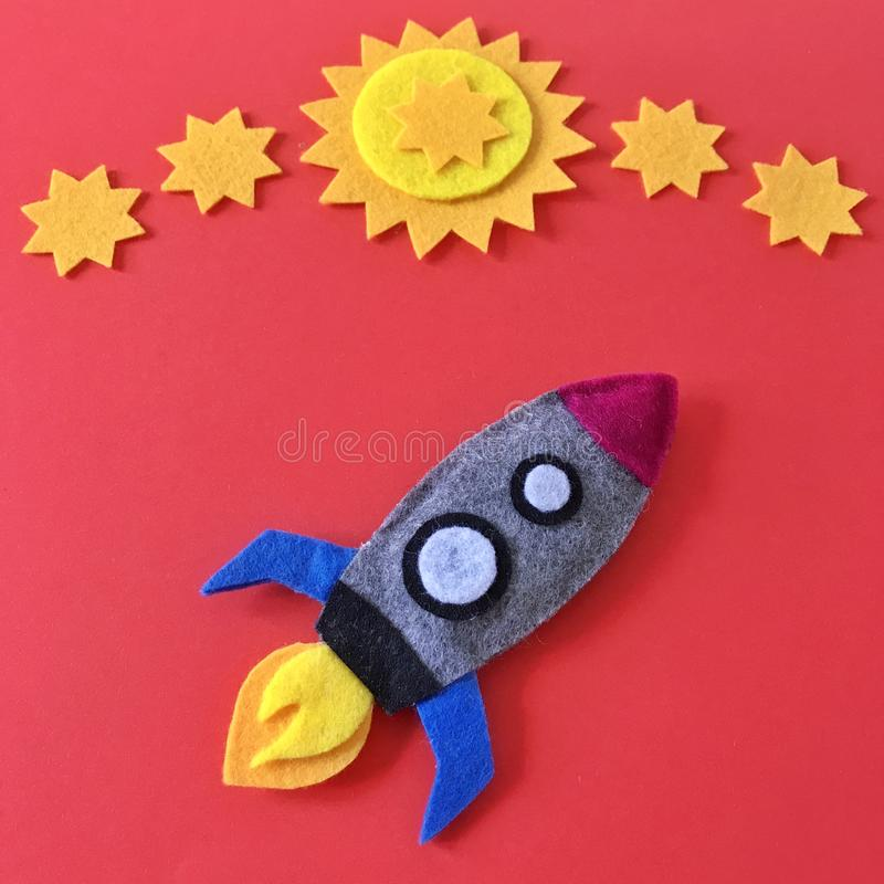 Felt Rocket Ship Flat Lay with Yellow Stars on Red. Colorful handmade rocket ship crafted with felt fabric. Yellow stars on red background with rocketship toy to royalty free stock photography