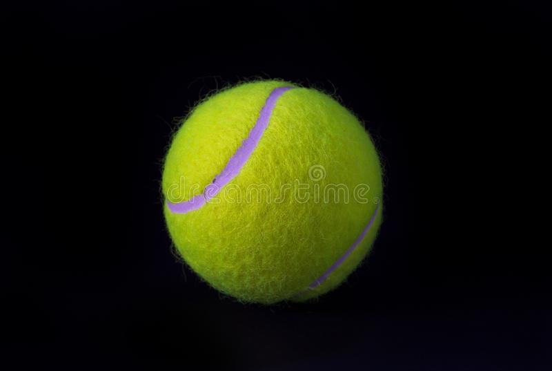 Felt tennis ball on black background. Tennis ball photo for banner template. Sport equipment isolated. Tennis competition backdrop. Yellow felt ball for active royalty free stock photography