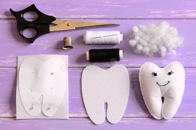 Felt tooth fairy, paper template, felt piece in a shape of a tooth, scissors, thread, needle, filler, thimble on table. Felt tooth fairy photo. Felt crafts for royalty free stock photo