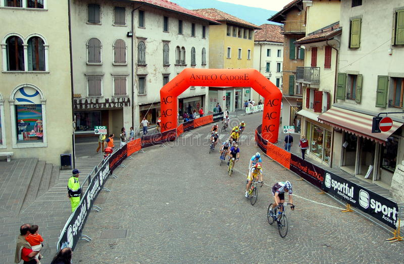 Feltre, Italy: Bicyclists Racing in Medieval City. Bikers participating in the Dolomiti Ski Civetta Falcade marathon race riding through the medieval town stock photo