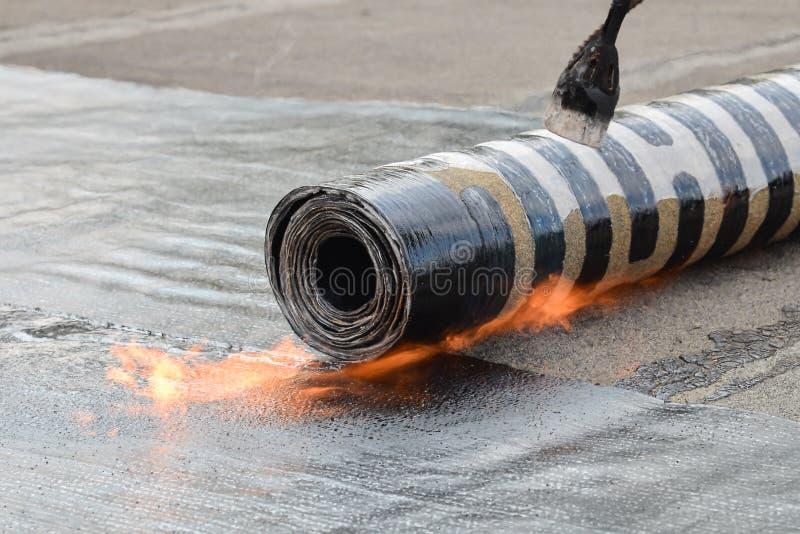 Feltro da instalação do telhado com aquecimento e rolo de derretimento do betume pela tocha na chama, tiro do detalhe do close up fotos de stock