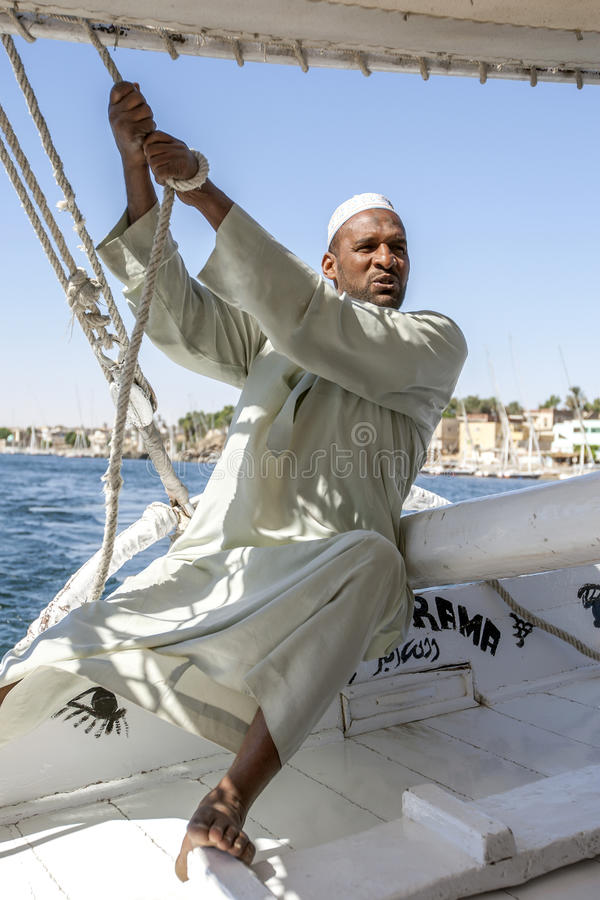 A felucca captain on the River Nile in Egypt. A felucca captain adjusts the sails of his boat whilst sailing down the River Nile in the Aswan region of Egypt royalty free stock image