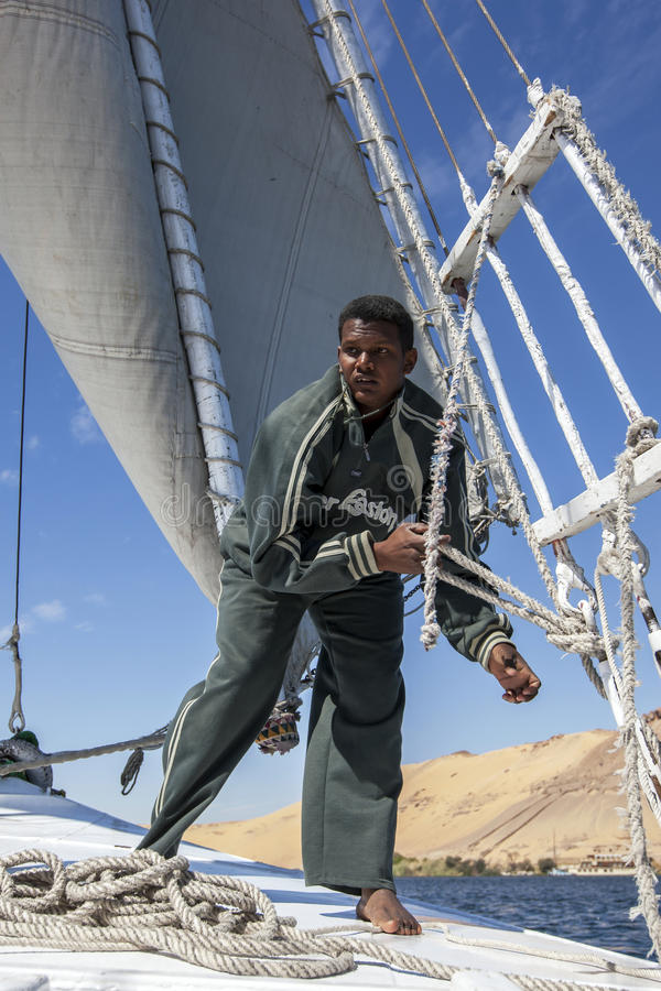 A felucca deckhand adjusts the sails whilst sailing down the River Nile in Egypt. A felucca deckhand adjusts the sails of his boat whilst sailing down the River stock images