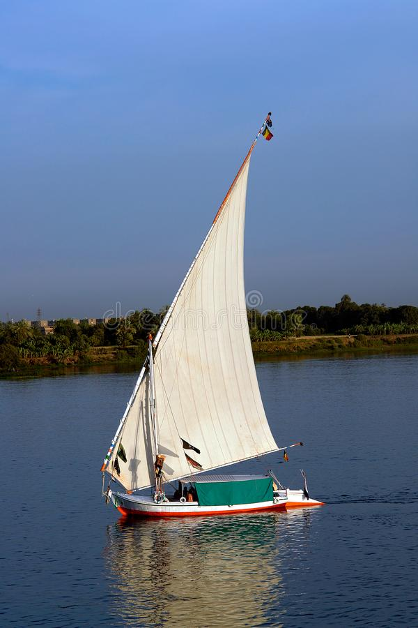 Felucca with white sails, sailing along the Nile River - Egypt. Felucca at dusk with white sails, sailing along the Nile River - Egypt royalty free stock image