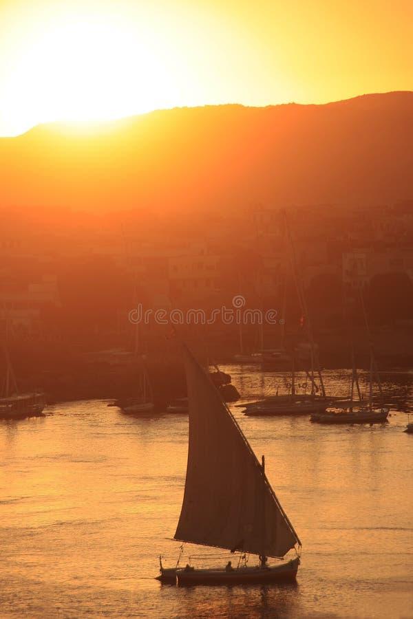 Felucca fartyg som seglar på Nilet River på solnedgången, Aswan fotografering för bildbyråer