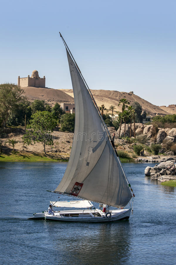 A felucca sailing down the River Nile in Egypt. A felucca captain adjusts the sails of his boat whilst sailing down the River Nile in the Aswan region of Egypt stock photography