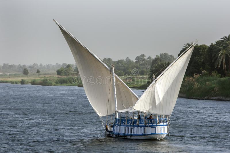 A felucca sails along the River Nile near Esna in central Egypt in the late afternoon. Tourists often cruise along the Nile from Luxor to Aswan aboard a stock images
