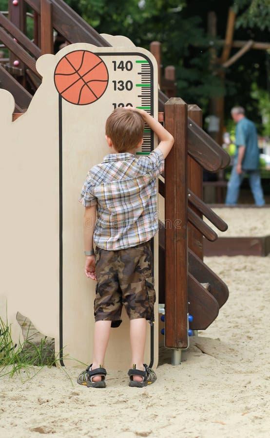 Femårig pojke som mäter hans höjd på lekplatsen royaltyfri foto