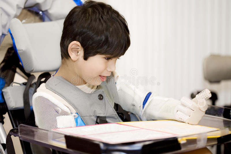 Femåring inaktiverad pojke som studerar i rullstol arkivfoto