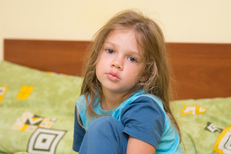 Fem-år flicka som upp vaknar sömnigt sammanträde på en säng royaltyfri foto