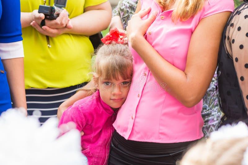 Fem-år flickaanseende i folkmassa och som klamra sig fast intill hennes moder arkivfoton