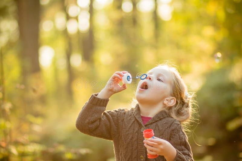 Fem år gammal caucasian barnflicka som blåser såpbubblor som är utomhus- på solnedgången - lycklig bekymmerslös barndom Nedgångse arkivfoto