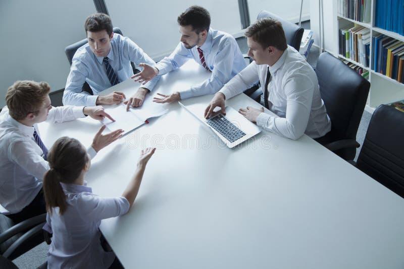 Fem affärspersoner som har ett affärsmöte på tabellen i kontoret arkivfoton