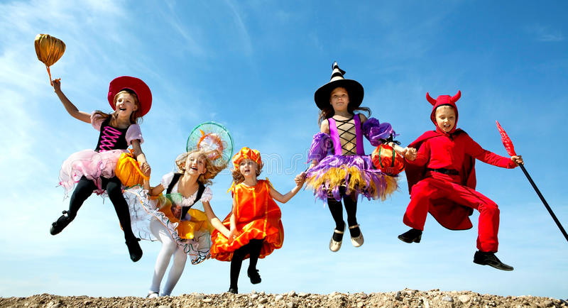 Fem allhelgonaaftonbarn som hoppar på den blåa himlen arkivfoto