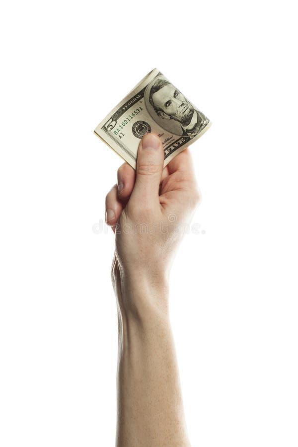 Fem amerikanska dollar kassapengar i den manliga handen som isoleras på vit bakgrund US dollar 5 sedel royaltyfri bild