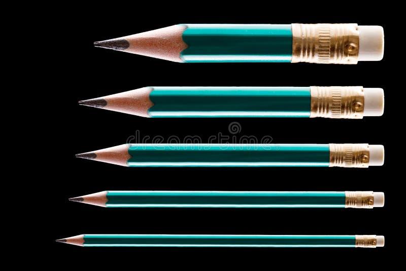 Fem blyertspennor på svart arkivfoto