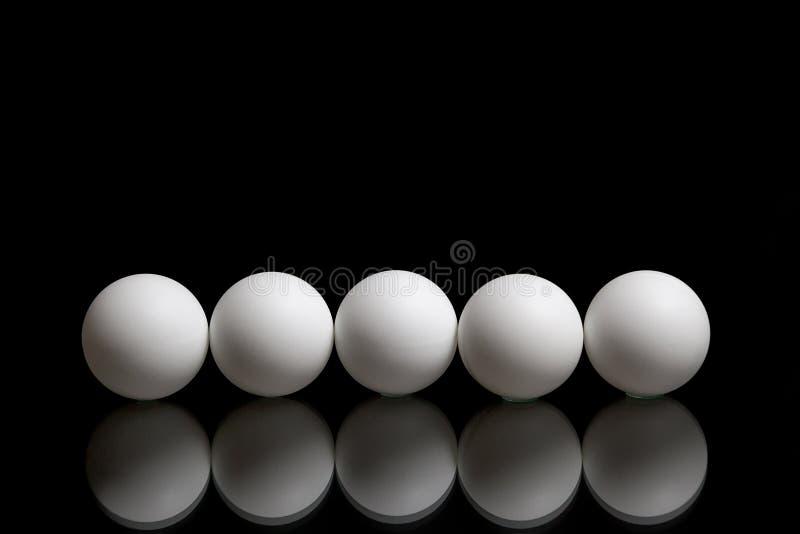 Fem bollar för knackar pong i rad på en mörk bakgrund royaltyfria bilder