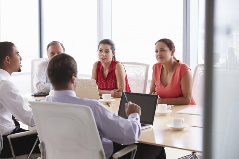 Fem Businesspeople som har möte i styrelse royaltyfri bild