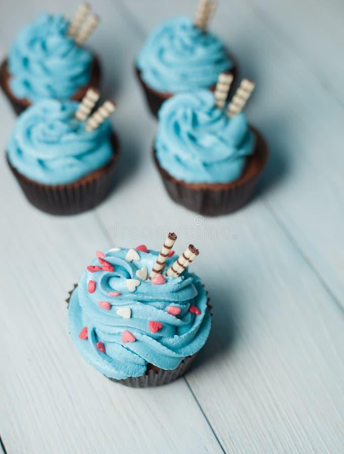 Fem capkakes med blått lagar mat med grädde med pulver i form av hjärtor royaltyfri fotografi
