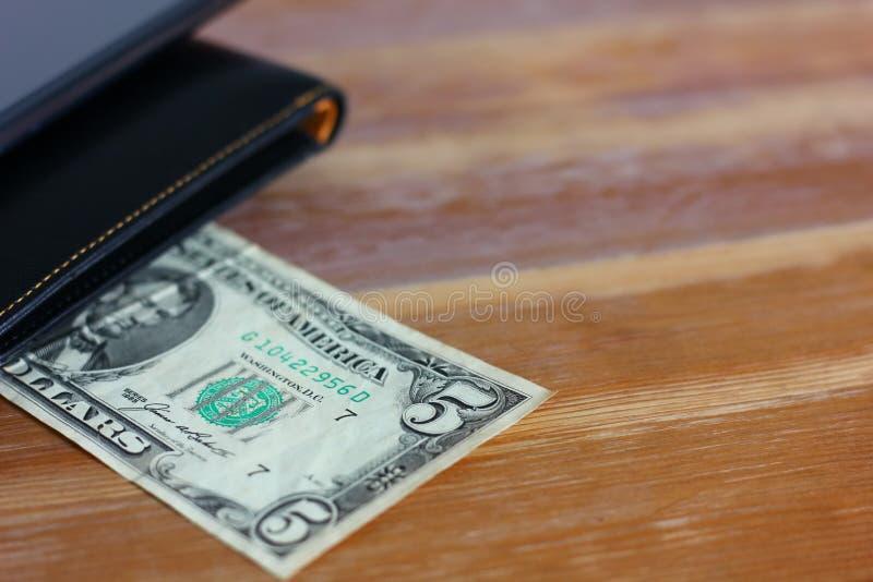 Fem dollar med svart piskar plånboken arkivbild
