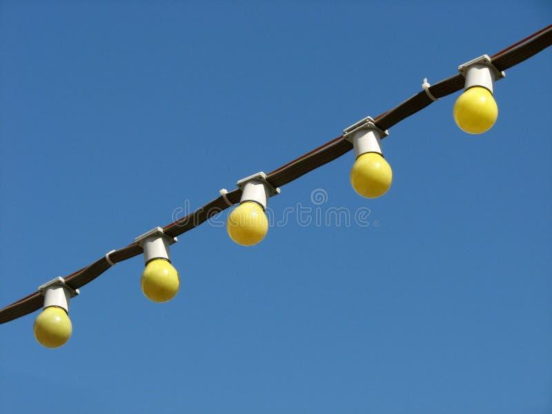 Fem gula glödande kulor på tråden på bakgrund för blå himmel fotografering för bildbyråer