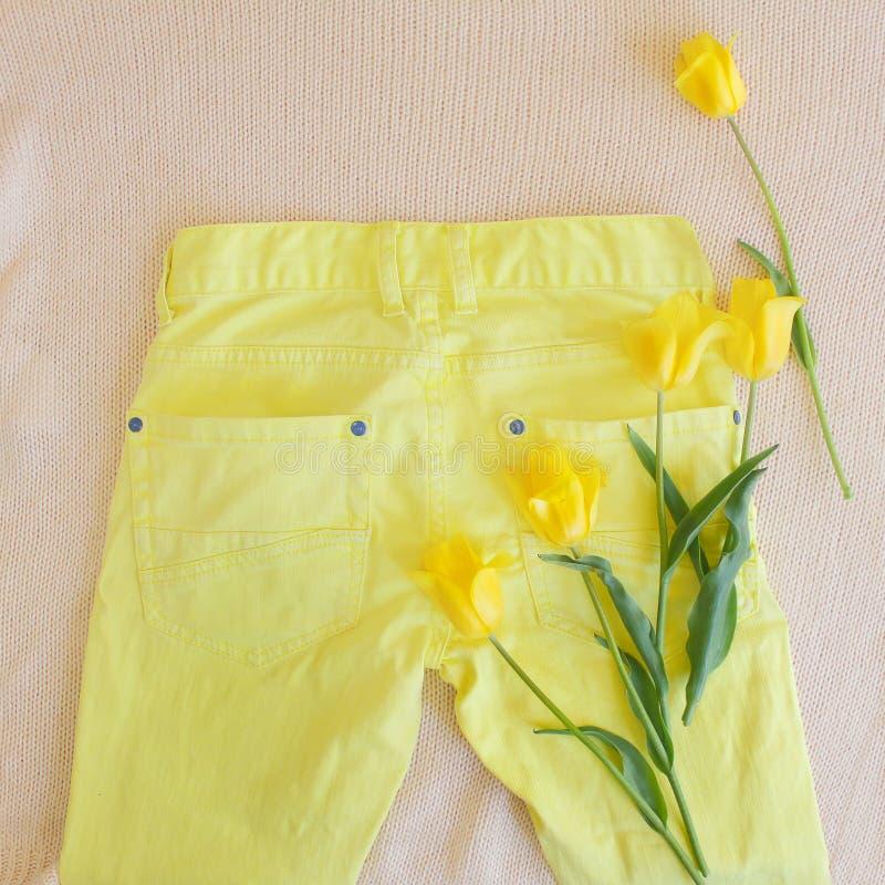 Fem gula tulpan på gul unisex- jeans Lekmanna- lägenhet Modespr fotografering för bildbyråer